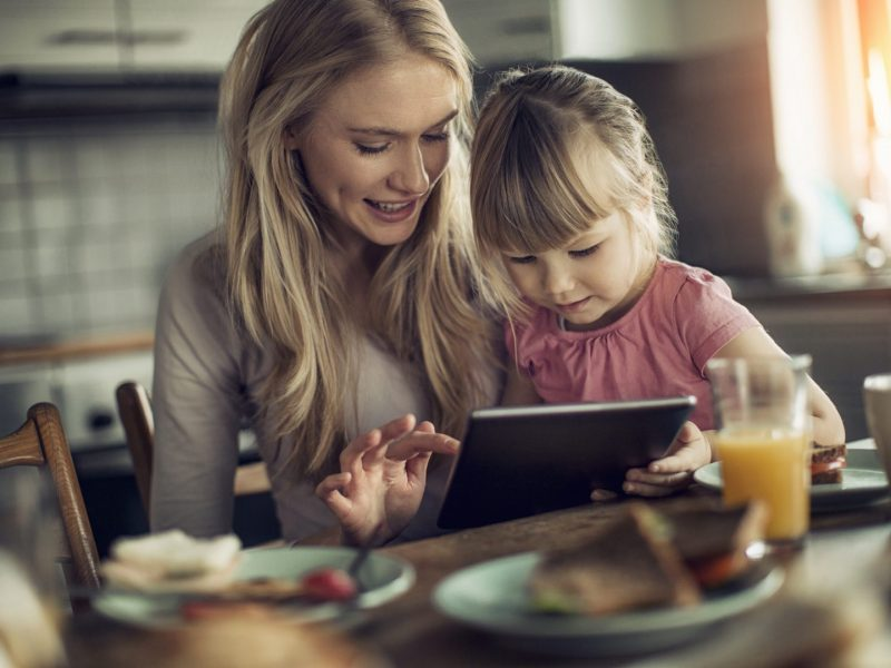 Picture of a mother and daughter having breakfast and surfing the net