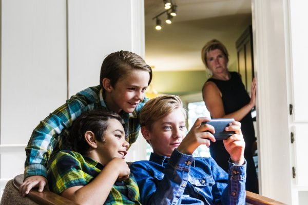 A mother looks on from the kitchen as three pre-teen boys use a smartphone in the living room.  She is out of focus but it is clear to see her sense of discomfort with what they are doing on the internet.