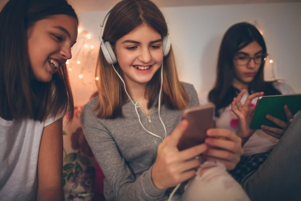 Smiling teenage girls using gadgets